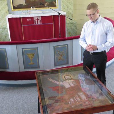Simon kirkkoherra Ville Väkeväinen uudelleen käyttöön vihittävän alttaritaulun äärellä Simon kirkossa.