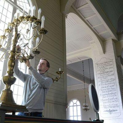 Kuvassa suntio Eero Raittila puhdistaa messinkistä valaisinta, kynttilälamput.