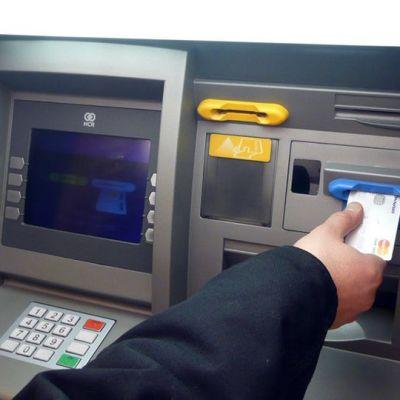 Käsi laittaa luottokorttia pankkiautomaatin siniseen kortinlukijaan.