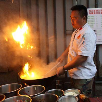 Kiinalaiskokki liekittämässä ruokaa.