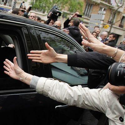 Nicolas Sarkozy vilkuttaa ihmisille autostaan lähtiessään äänestyspaikalta.