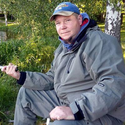 Mies istuu vehreällä rantapöyräällä ja onkii