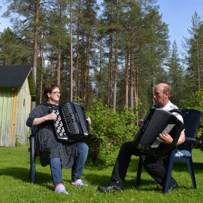 Lea Taipale ja Martti Turunen soittavat haitareita puutarhatuoleissa pihamaansa keskellä.