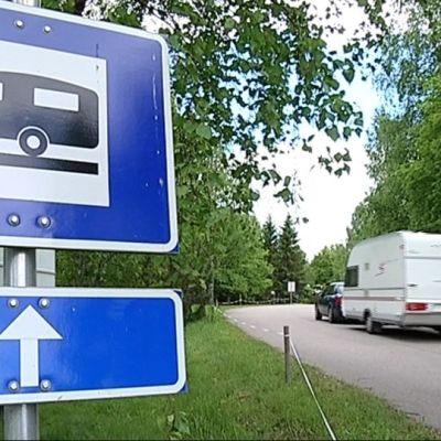 Asuntovaunua vetävä henkilöauto ohittaa asuntovaunua kuvaavan liikennemerkin.