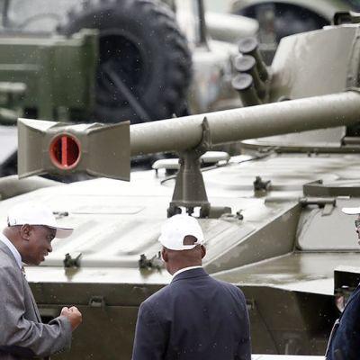 Kolme miestä panssarivaunun edessä.