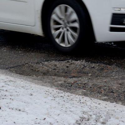 Auto ohittaa kuopan tiellä.