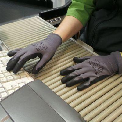 Myyjä näppäilee kassakonetta hanskat kädessään