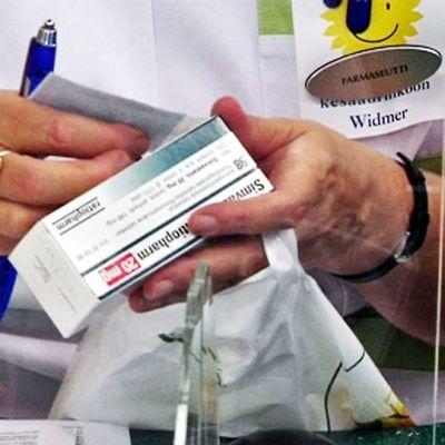 Kilpailuvirasto epäilee, että apteekit eivät aina myy halvimpia rinnakkaistuontilääkkeitä, vaikka pitäisi. Apteekissa käsitellään lääkepakettia.