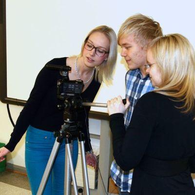 Kolme nuorta videokameran ympärillä
