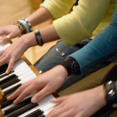 Musiikkiluokkalaiset tuntevat suurempaa yhteenkuuluvuutta kuin tavallisessa koululuokassa opiskelevat. Kaksi tyttöä soittavat yhdessä pianoa.