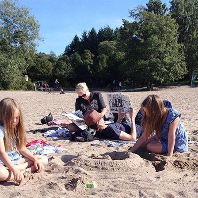Perhe kesäisellä hiekkarannalla syyskuussa.