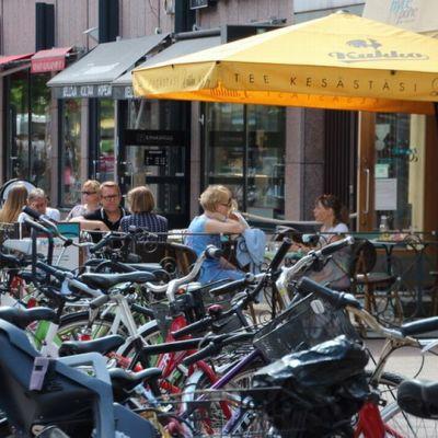 Ihmisiä kesäterassilla kävelykatu polkupyöriä