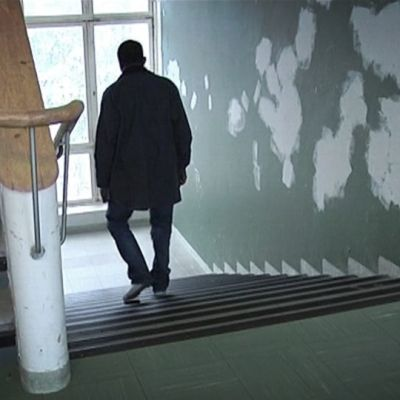 Mies kävelee portaita alas ränsistyneessä rappukäytävässä.