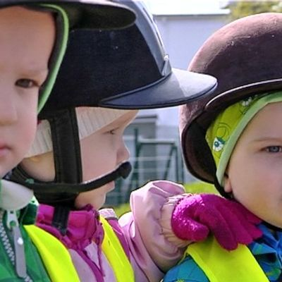 Pieniä lapsia ratsastuskypärät päässä.