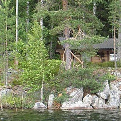 Kesämökki kallioisen järven rannalla.