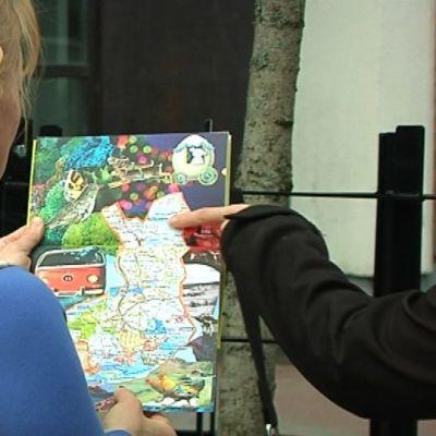 Nainen katsoo Suomen karttaa. Toisen naisen sormi osoittaa kartalla paikkaa Pohjois-Suomessa.