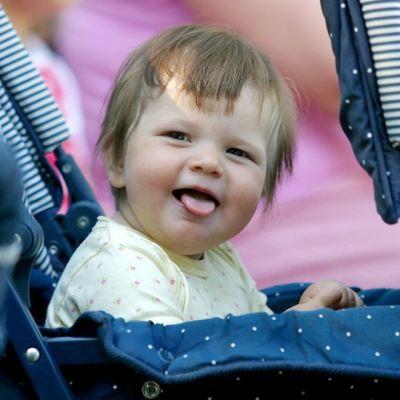 Lapsi istuu vaunuissa kieltä näyttäen.