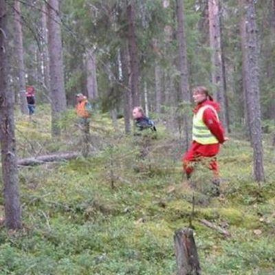 Ihmisiä metsässä.