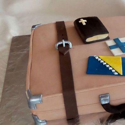 Kuvassa ruskea vanhanaikainen matkalaukku, Jossa Suomen ja Bosnian liput ja raamattu.