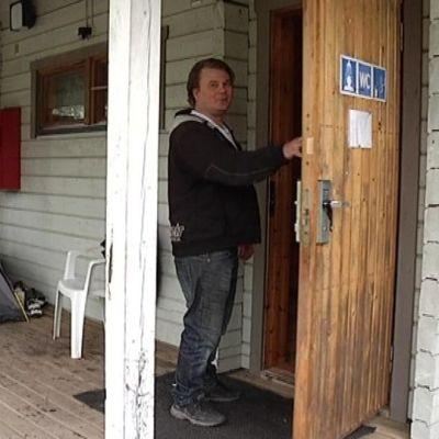 Alhovuoren entinen omistaja Tom Puusa huoltorakennuksen ovella.