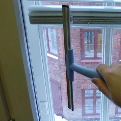 Ikkunaa kuivataan lastalla.