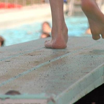 Jalat ponnahduslaudalla ja uimareita taustalla.