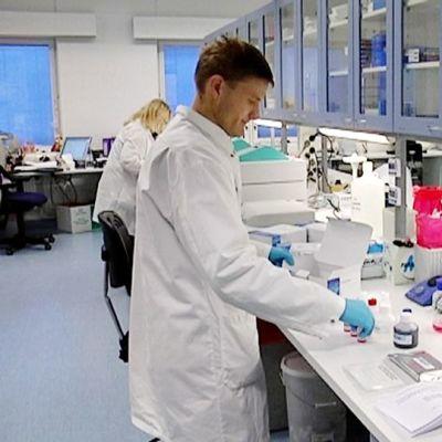 Laborantti nostelee pulloja pöydälle laboratoriossa.