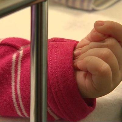 Vauvan käsi näkyy sairaalasängyn välistä.