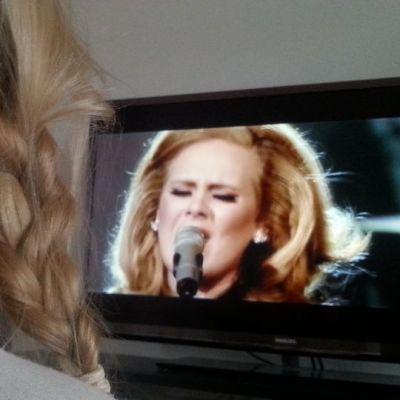 Palmikkopäivnen tyttö katsoo television lauluohjelmaa.