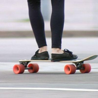 Nainen skeittaa longboardilla kaduilla.