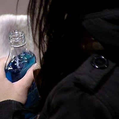 Nuori nainen pitää kädessään minttulikööripulloa.