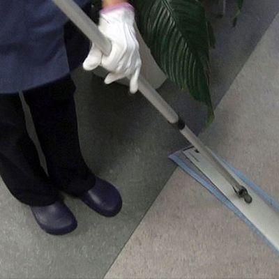 Siivooja luutuaa lattiaa.