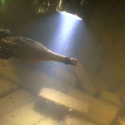 Sukeltaja valaisee lampulla merenpohjassa maannutta samppanjapulloa.