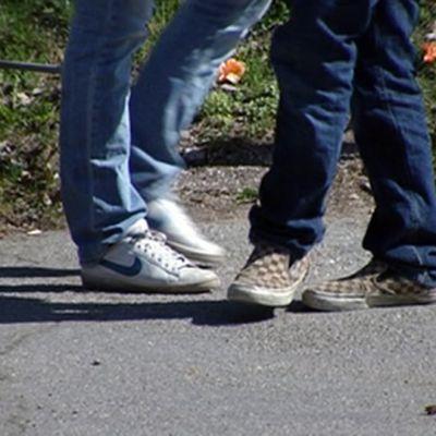 Kaksi anonyymia nuorta seisoo asfaltilla.
