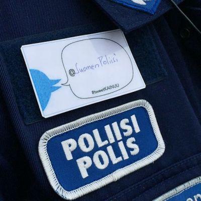 Poliisi-rintamerkki poliisin asussa ja @SuomenPoliisi-tunnus paperilapussa.