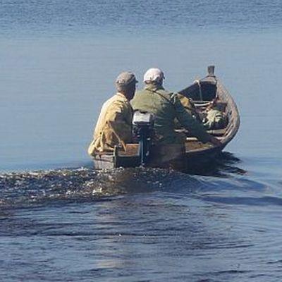 Kaksi miestä veneessä järvellä.