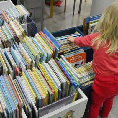 Lapsi tutkii kirjaston kirjoja.