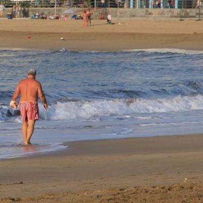 Kuvassa mies kävelee vesirajassa hiekkarannalla Gran Kanarialla Las Palmasissa.