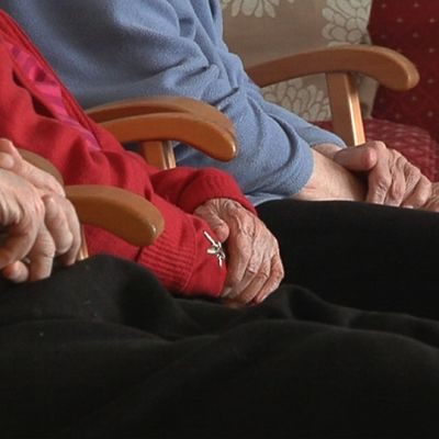 Vanhukset istuvat kädet sylissä vierekkäin.