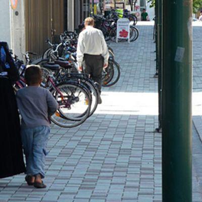 Romaaniäiti lapsensa kanssa kadulla.