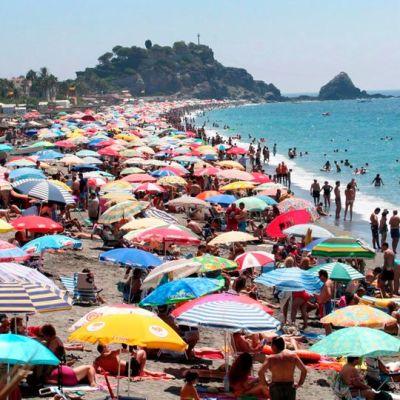 Ihmiset ottavat aurinkoa Espanjan San Cristobalissa.