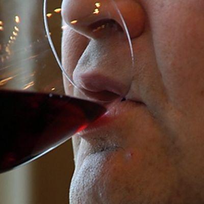 Mies juo punaviiniä lasista.