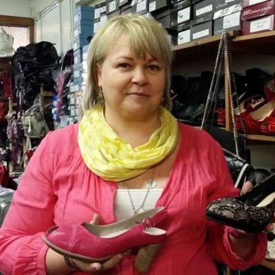 Kuvassa nainen pitää käsissään kahta kenkää.