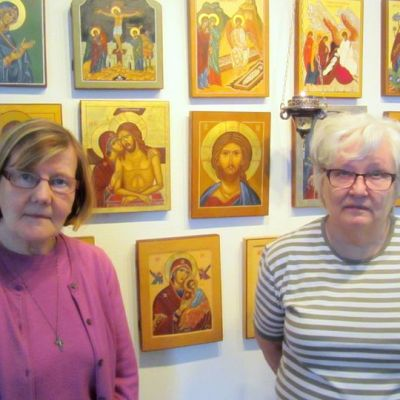 Kaksi naista seisoo ikonien edessä.