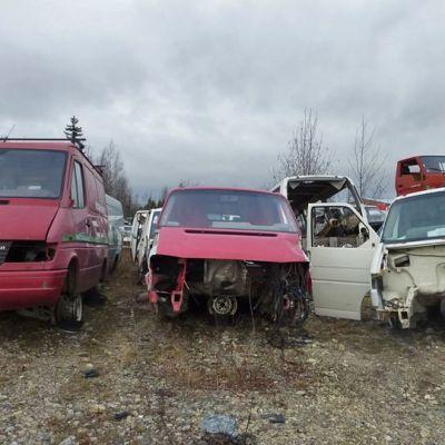 Puoliksi puretut autot rivissä purkamon pihassa.