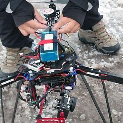 Kuvauskopteri maassa ilman kantta, mies käsittelee laitetta