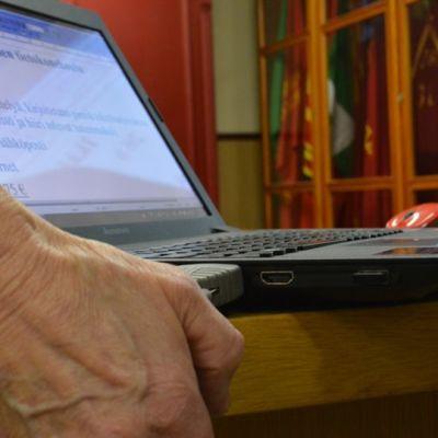 Kannettava tietokone ja pöytään nojaava vanhuksen käsi.