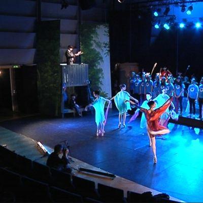 Kuvassa musiikkinäytelmä Outolinnun harjoitukset. Lavalla näyttelijöitä, balettitanssijoita ja kuorolaisia.
