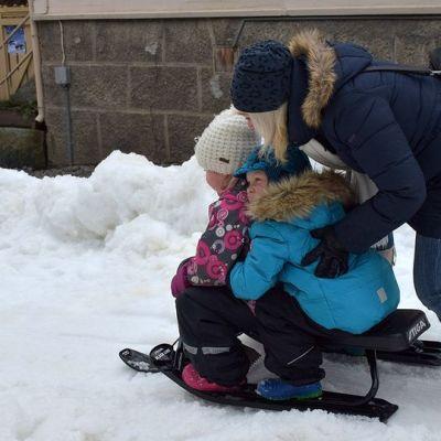 Äiti antaa vauhtia rattikelkassa istuville lapsilleen