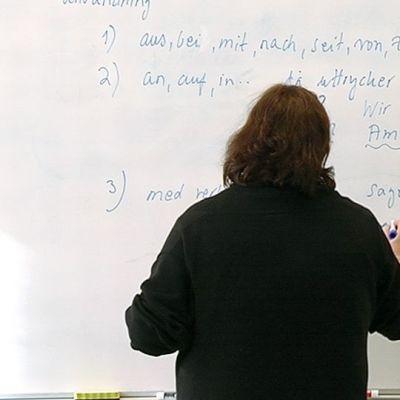 Opettaja kirjoittaa taululle.